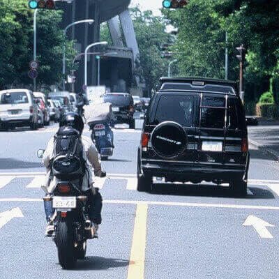 オートバイで尾行調査をする探偵
