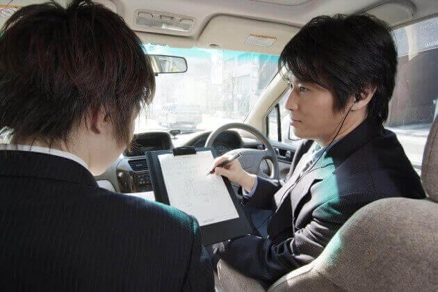 車内で調査内容を確認する探偵