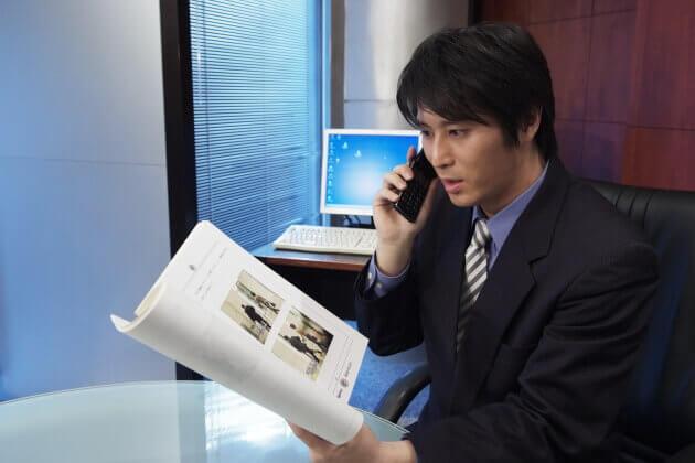 裁判資料を手に電話説明をする探偵